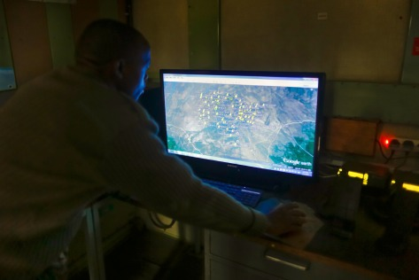 A computer screen showing GPS-tracked anti-poaching patrol units is monitored by a radio operator in the radio room at Ol Pejeta.
